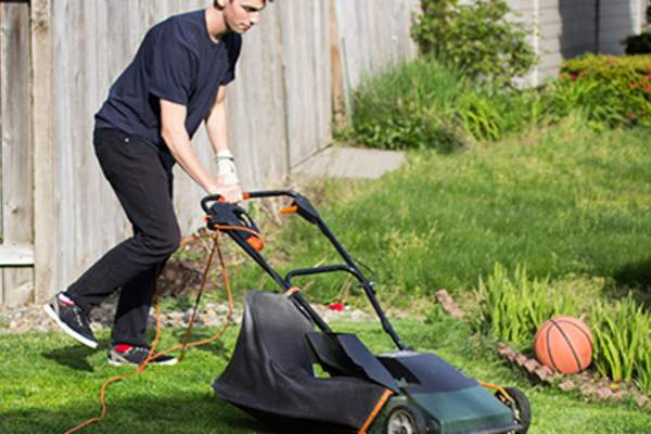 Teen boy mowing the lawn.