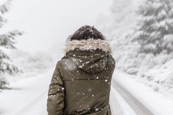 woman wearing hooded jacket in blizzard