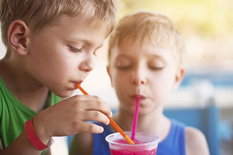 Two young boys drinking a sugary beverage with colorful straws.