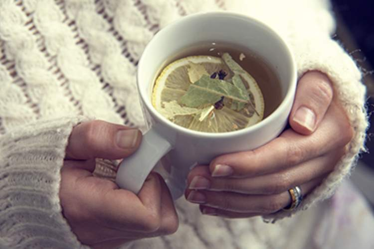 Woman holds a cup of tea with lemon.