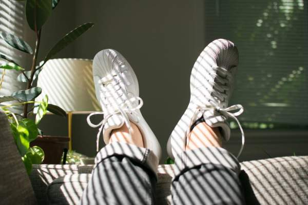 sneakers and bare ankles on couch