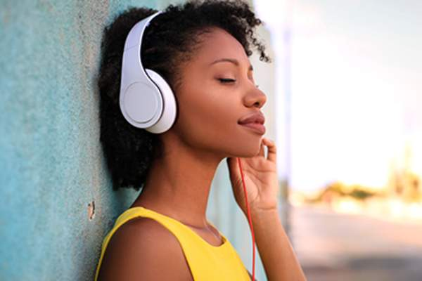 Young woman listening to music through headphones.