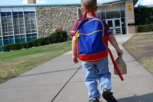 Little boy walking into school with backpack.