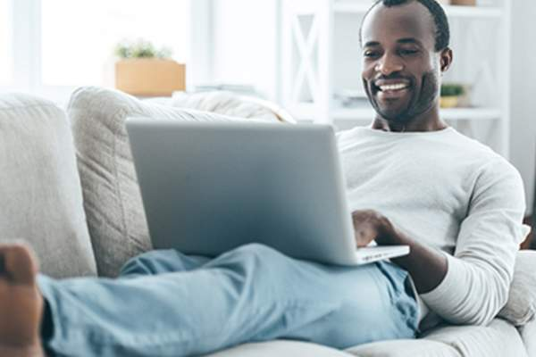 Man using a laptop at home on the couch.