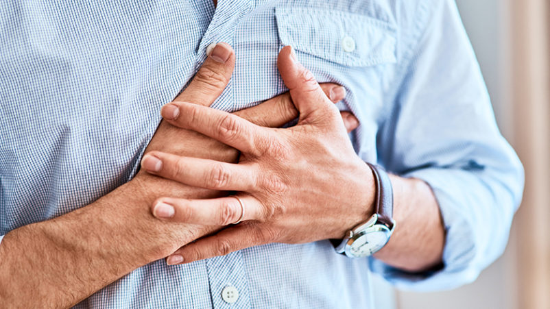 Man with heart pain clutching his chest.