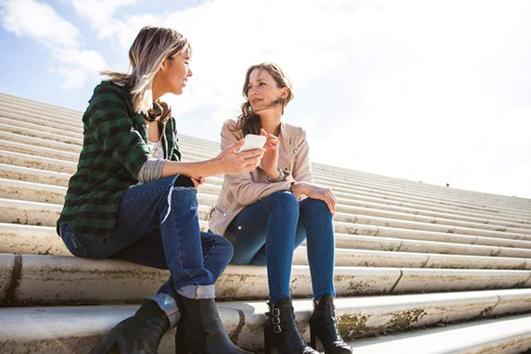 Two young women sitting on stairs talking and having coffee.