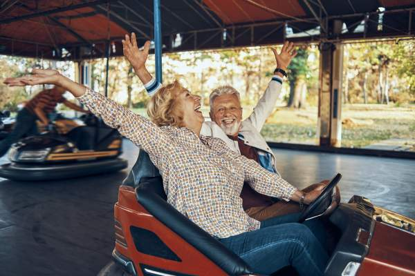 senior couple riding bumper cars