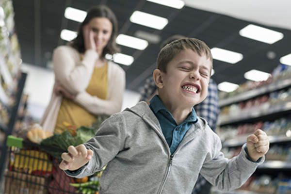 Child with dysmorphic mood dysregulation disorder having an outburst in a supermarket.