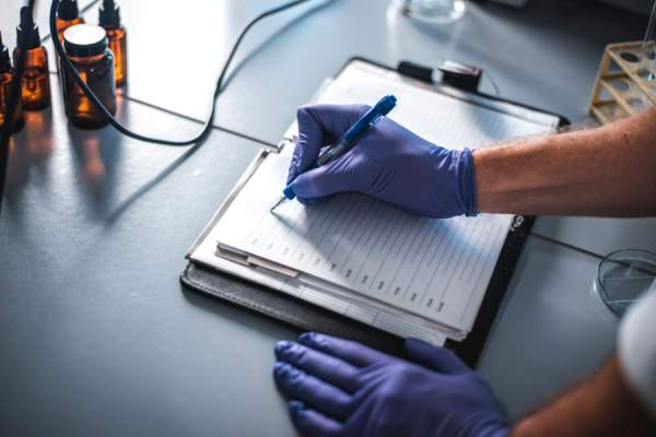 scientist wearing gloves in lab writing in journal