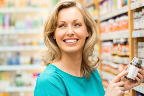 Smiling woman in supplements aisle of store.