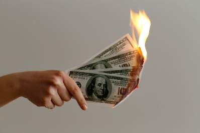 hand holding 100 dollar bills on fire
