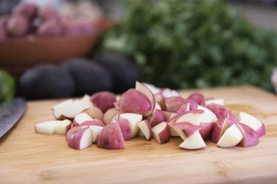 Red cut potatoes on cutting board.