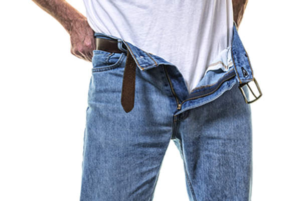 Man putting on jeans.