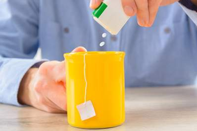 Man adding artificial sweetener to cup of tea.