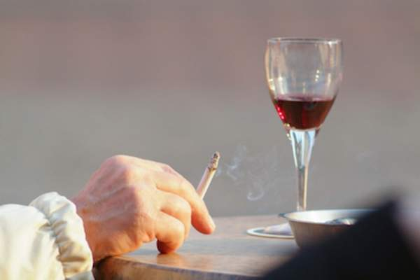 Hand with cigarette and glass of red wine.