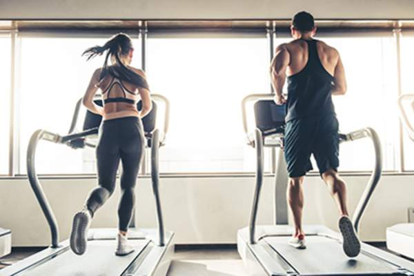 Man and woman running side by side on treadmills at the gym.