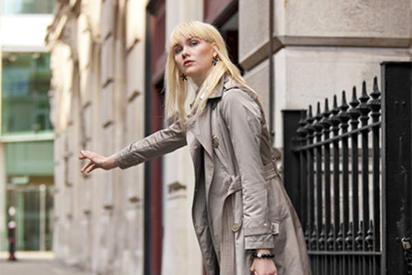 Young woman wearing a khaki trench coat hailing a taxi.