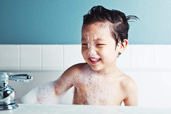 Child taking a bubble bath.