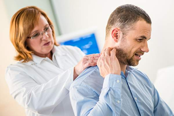Doctor examining a man's painful neck.