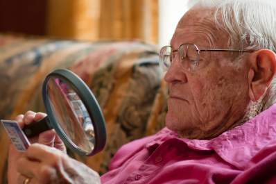 Senior man reading with magnifying glass.
