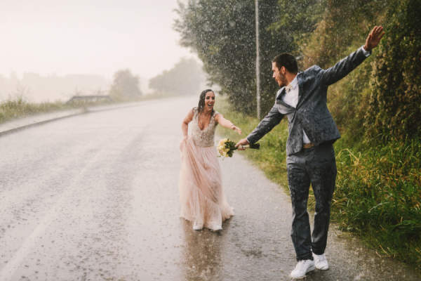bride and groom happy in the rain