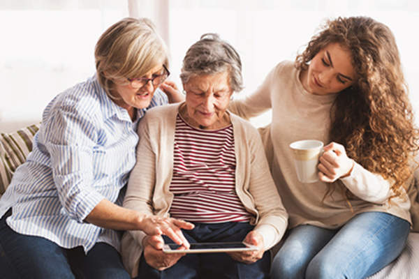 Three generations of women using a tablet.