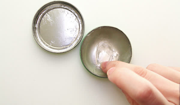 Female fingers scooping petroleum jelly from tin.