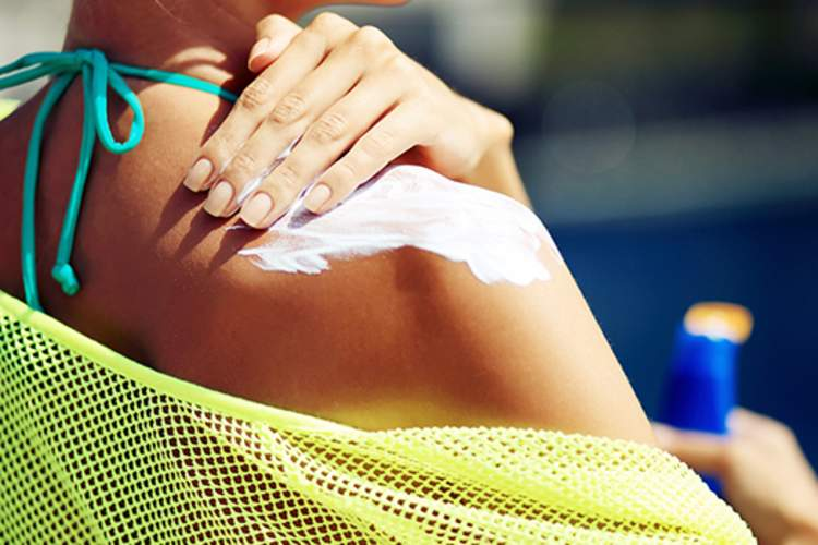 A woman applies  sunscreen to her shoulder.