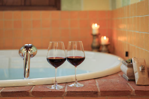 Wine glasses on the rim of a bathtub