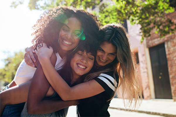 Three young women friends, smiling and hugging.