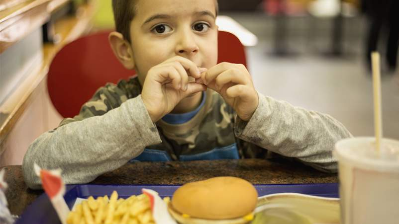 Young boy eating fast food kids' meal.