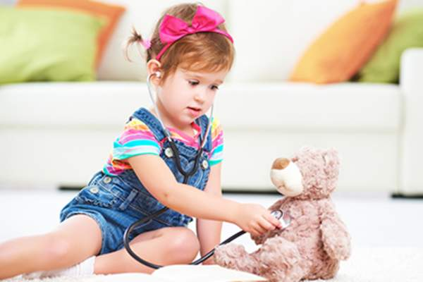 Little girl playing quietly with stuffed bear.