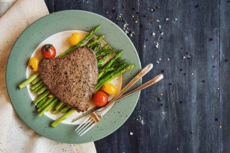 Tenderloin steak with grilled asparagus and cherry tomatoes.