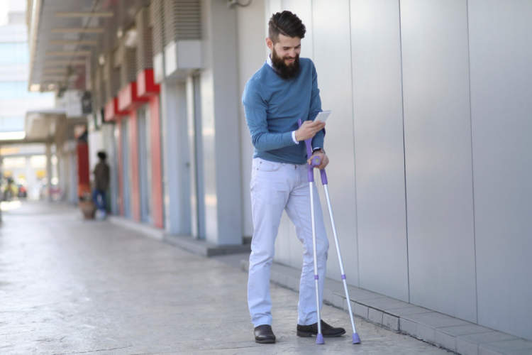 young bearded man with arm crutches texting