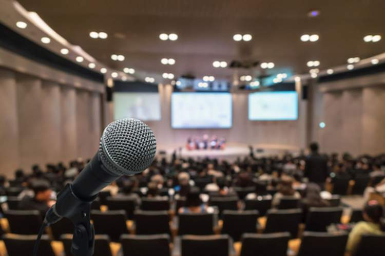 A microphone with a conference hall in the background.