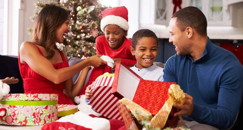 Parents opening Christmas presents with their children.