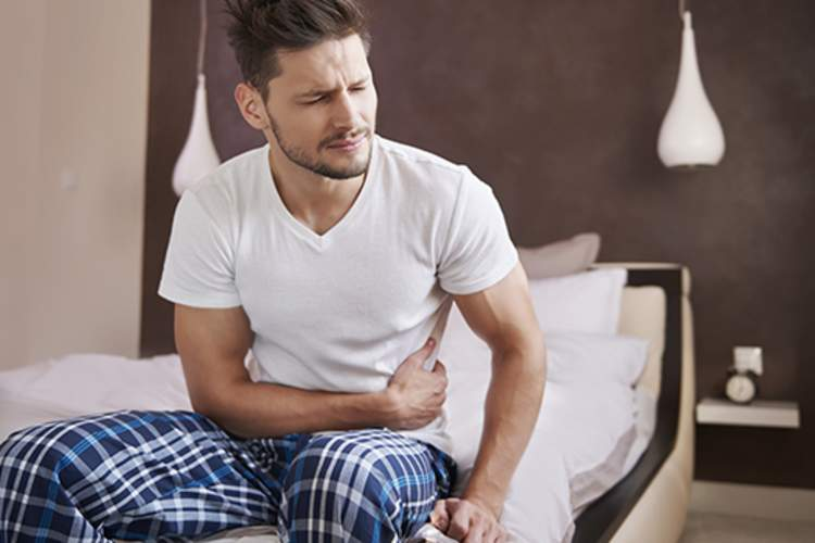 Man experiencing abdominal pain in bed