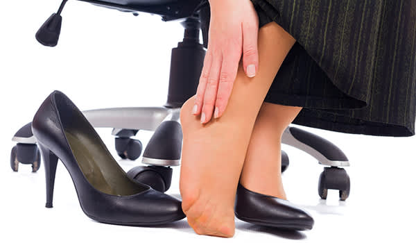 Woman with foot pain at work, shoe off, rubbing foot.