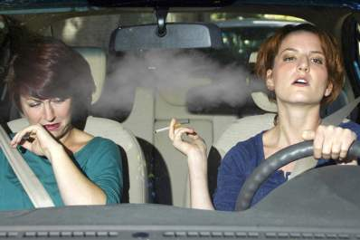 Two women in car with secondhand smoke from cigarette.
