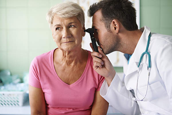Doctor checking a senior patient's ears.
