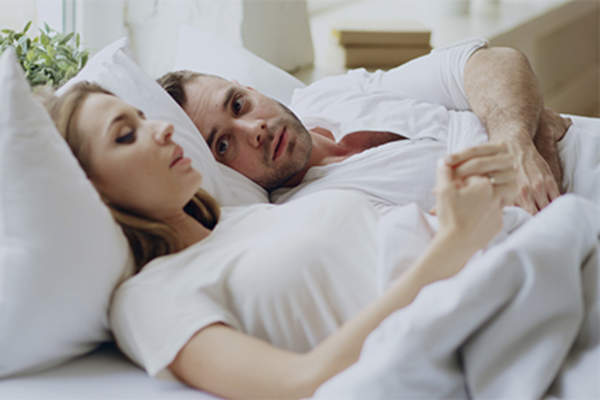 Young couple talking in bed.