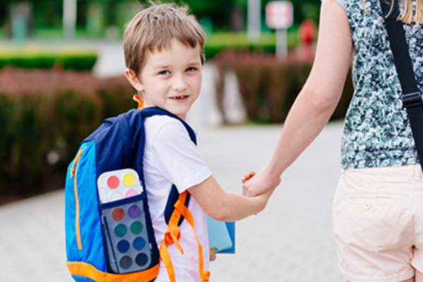 Child wearing a backpack walking to school with his mom.