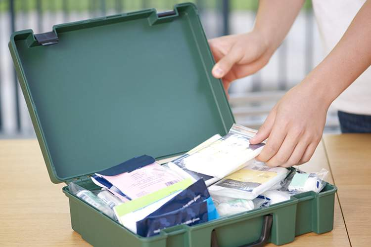 Woman packing an emergency medical supplies kit.