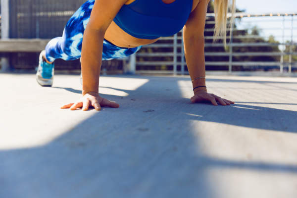 woman in blue sports bra doing push ups