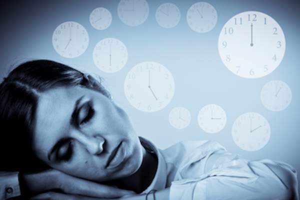 Circadian rhythm concept, clocks spinning around sleeping woman.