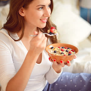Woman in pajamas in bedroom eating muesli with berries
