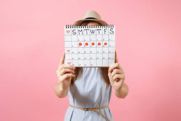 Portrait of woman in blue dress covering face, hiding behind periods calendar for checking menstruation days