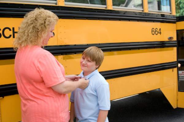 Mother buttons her child's shirt before he boards the school bus.