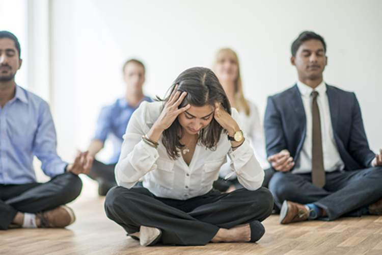 People in a meditation class, one woman frustrated.