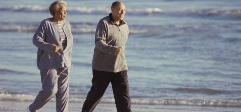 older couple briskly walking beach